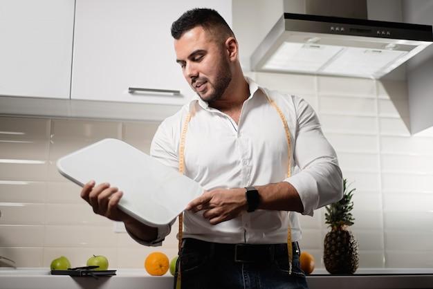 Мужской диетолог холдинг весы на кухне.