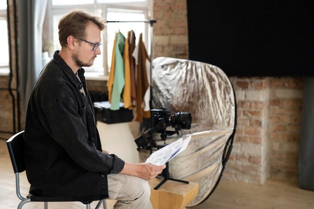 彼の新しい映画の脚本を見ている男性監督