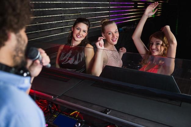 Male disc jockey playing music with three women dancing on the dance floor