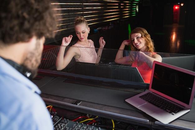 댄스 플로어에서 춤을 추는 두 여자와 음악을 연주하는 남성 디스크 자키