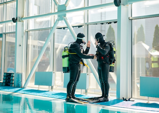 Male diver and divemaster in scuba gear, dive lesson in diving school. teaching people to swim underwater, indoor swimming pool interior on background
