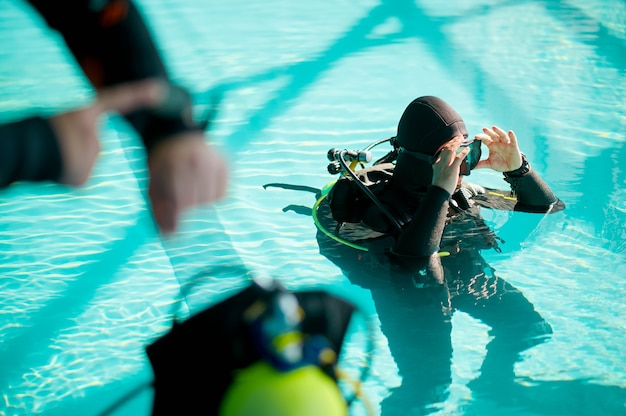 Male diver and divemaster in scuba gear mark the dive time, diving school. teaching people to swim underwater, indoor swimming pool interior on background