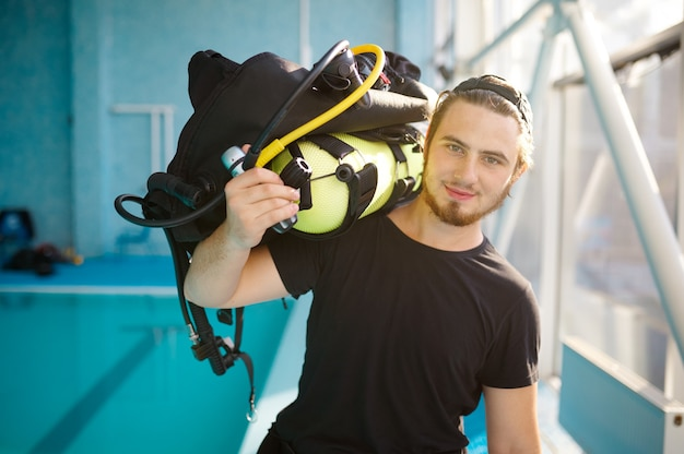 Male diver holds scuba gear, course in diving school. teaching people to swim underwater, indoor swimming. man with aqualang or oxygen tank