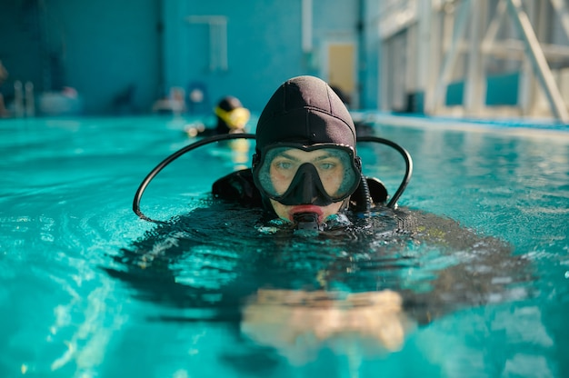 Дайвер-мужчина в акваланге и маске позирует в бассейне