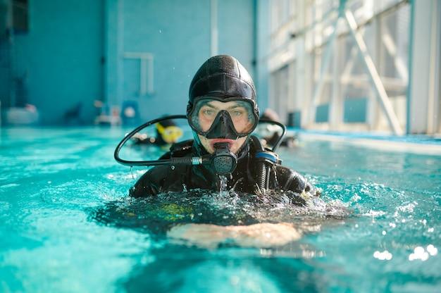 스쿠버 장비와 마스크를 쓴 남성 다이버가 수영장에서 포즈를 취하고 있습니다.