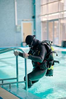 스쿠버 장비를 입은 남성 다이버가 수영장에서 나옵니다.