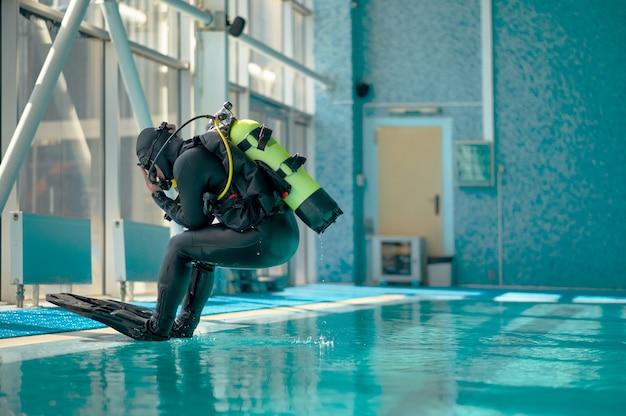 Дайвер-мужчина в акваланге прыгает в бассейн