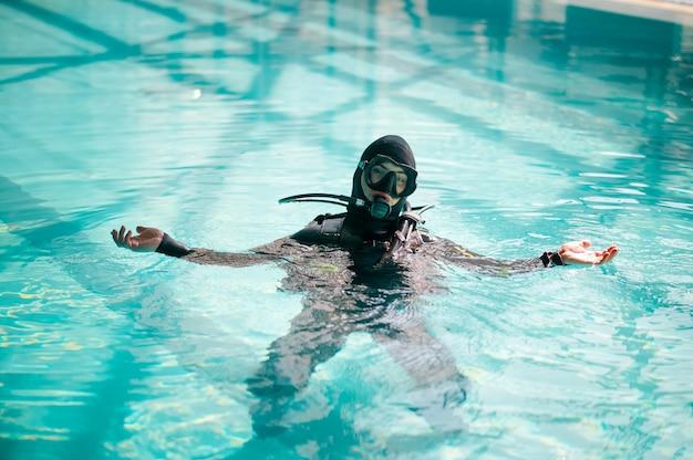 Мужчина-дайвер в акваланге позирует в бассейне, дайвинг