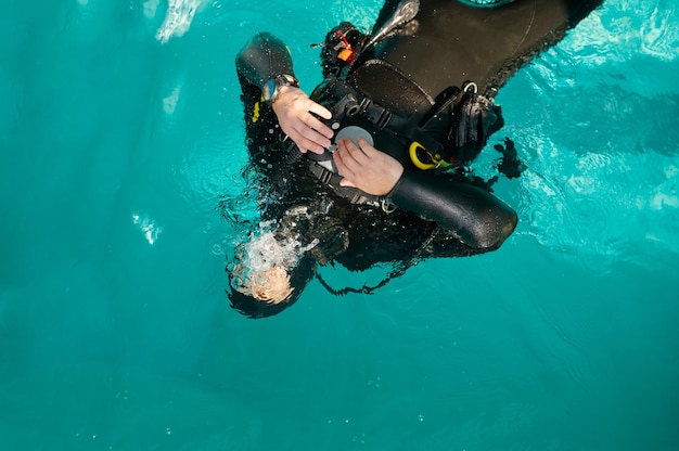 스쿠버 장비를 입은 남성 다이버가 수영장에서 포즈를 취하고 있습니다.