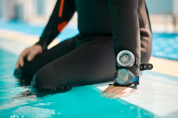 Мужчина-дайвер в акваланг, сидя у бассейна