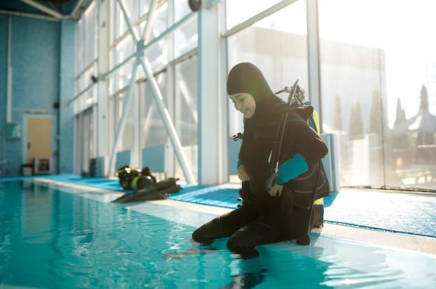 스쿠버 슈트를 입은 남성 다이버가 수영장 옆, 다이빙 학교에 앉아 있습니다. 사람들에게 수중 수영을 가르치고, 배경에 실내 수영장 내부