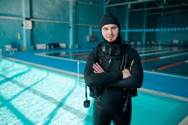 남성 다이버는 스쿠버 슈트, 다이빙 학교에서 포즈를 취합니다. 사람들에게 수중 수영을 가르치고, 배경에 실내 수영장 내부