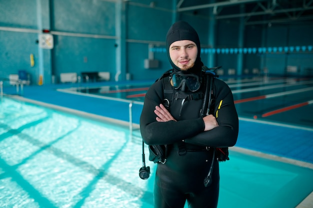 Male diver poses in scuba suit, diving school. teaching people to swim underwater, indoor swimming pool interior on background