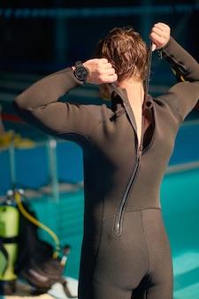 Male diver puts on scuba gear, diving school