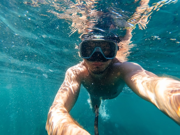Male diver swims in the sea under the blue water with a mask and snorkel