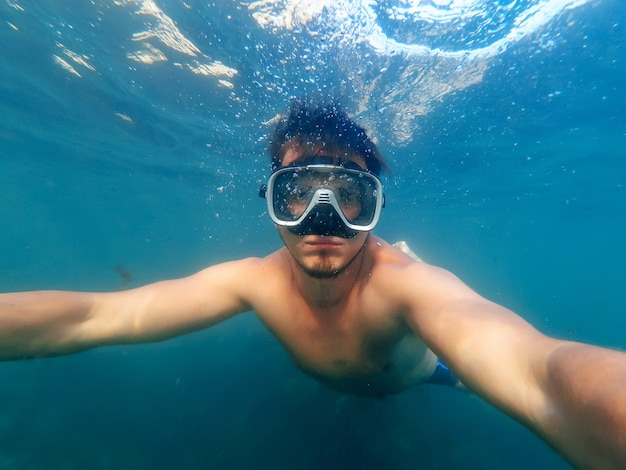 Male diver swims in the sea under the blue water with a mask