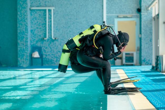 스쿠버 장비를 입은 남성 다이버들이 수영장으로 뛰어듭니다.