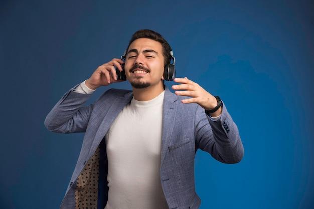 Male dj in grey suit wearing headphones and relaxing.