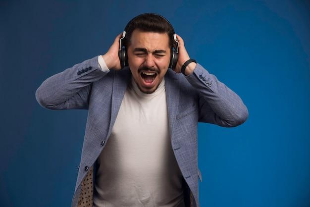 Dj maschio in abito grigio che indossa le cuffie ad alto volume e urlando.