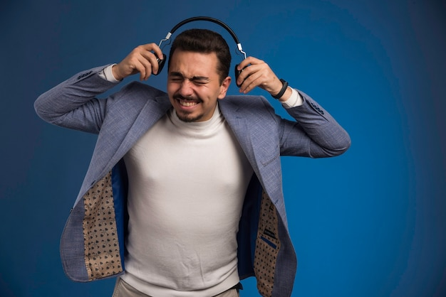 Male dj in grey suit wearing headphones with high volume.
