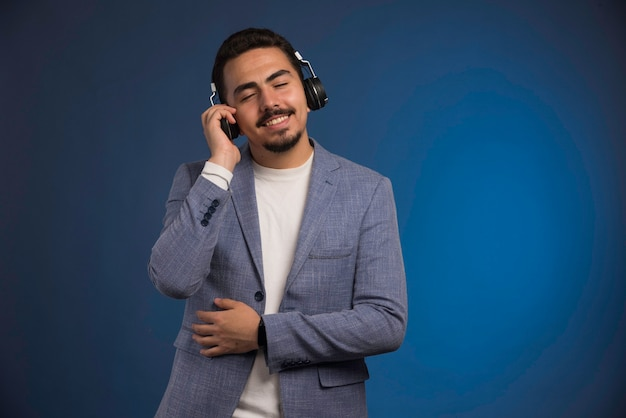 회색 양복을 입은 남성 dj가 헤드폰을 듣고 편안하게 느낍니다.