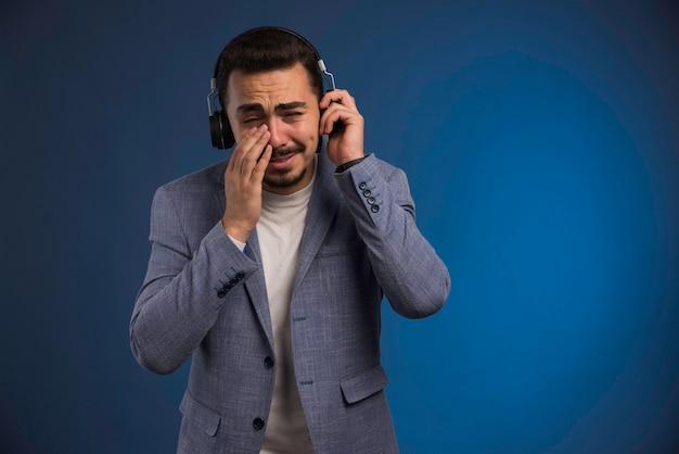 회색 양복을 입은 남성 dj가 헤드폰을 듣고 감동받습니다.