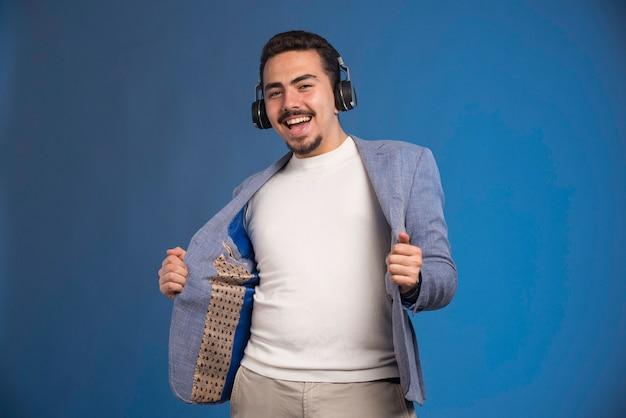 헤드폰을 착용하고 춤을 회색 양복을 입은 남성 dj.