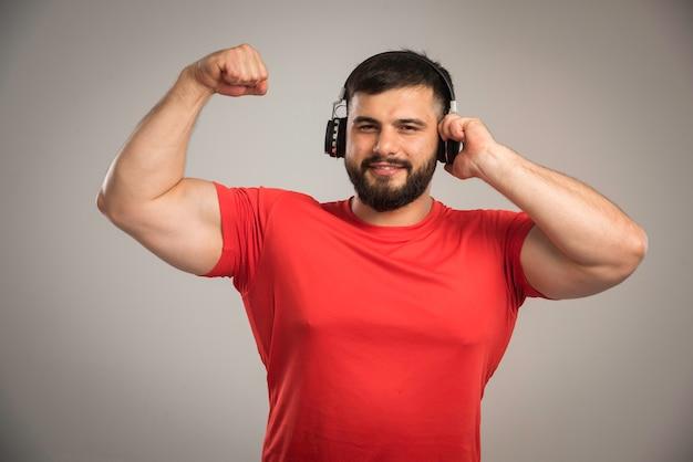 ヘッドフォンを着用して楽しんでいる赤いシャツの男性dj。