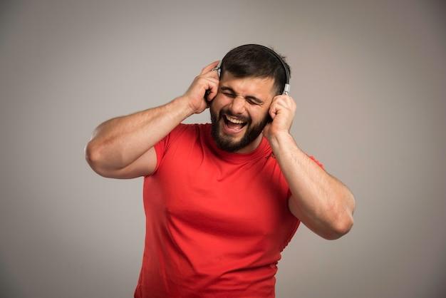 ヘッドフォンを着用して歌う赤シャツの男性dj