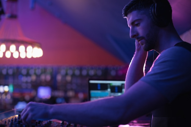 Male dj listening to headphones while playing music