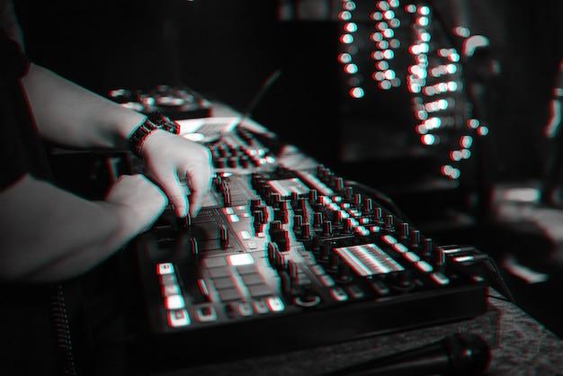 男性djは、パーティーのナイトクラブでプロの音楽コントローラーで電子音楽をミックスします。バーチャルリアリティグリッチ効果のある白黒写真