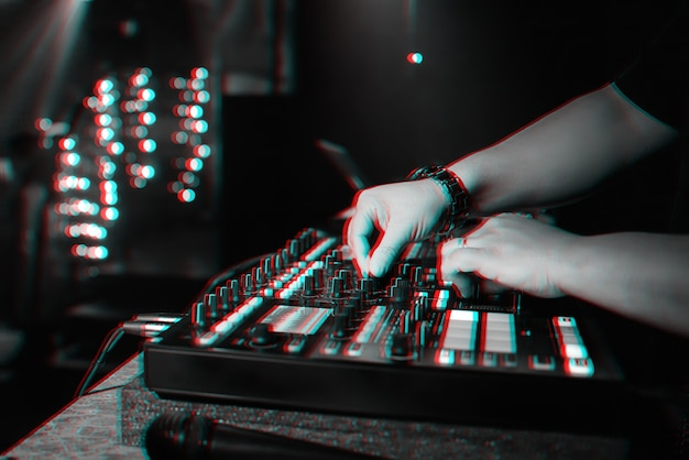 Male dj mixes electronic music on a professional music controller in a nightclub at a party.