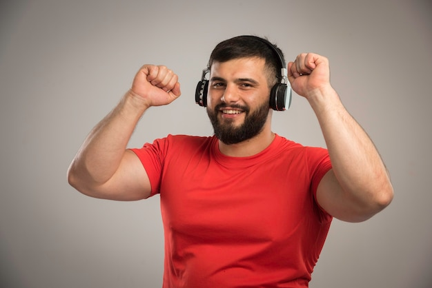 Male dj in red shirt wearing headphones and listening to music while dancing