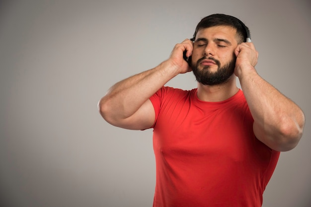 Male dj in red shirt wearing headphones and listening to music.