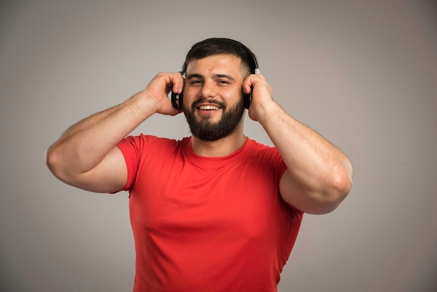 Dj maschio in camicia rossa che indossa le cuffie e ascolta la musica.