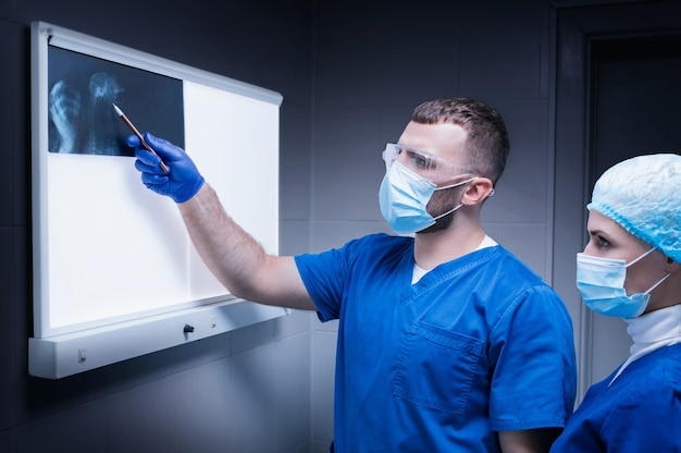 Врач-мужчина и медсестра стоят возле негатоскопа и изучают рентгеновский снимок раненого животного. концепция ветеринарной медицины. смешанная техника