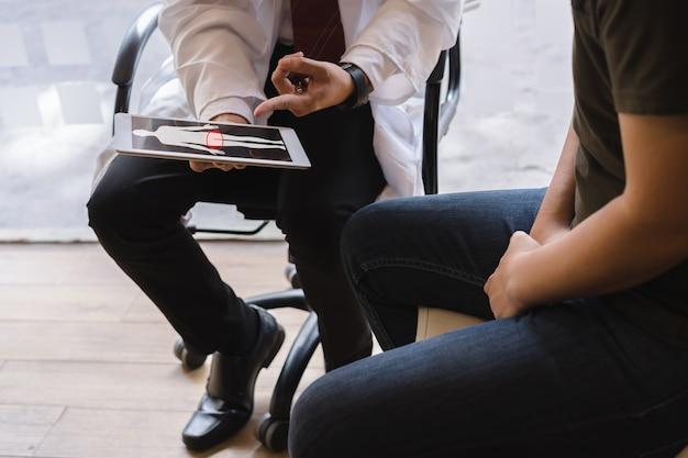 남성 의사와 고환암 환자는 고환암 검사 보고서에 대해 논의하고 있습니다. 고환암과 전립선 암 개념.