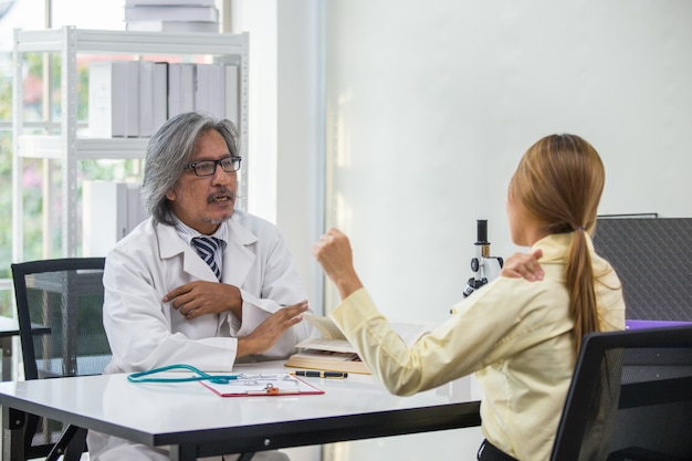 Male doctor asian, check patient woman shoulder pain in laboratory