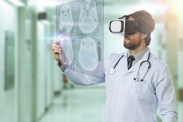 Врач-мужчина в больнице, используя очки виртуальной реальности, смотрит на виртуальный экран