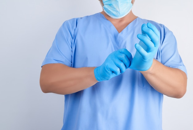 Male doctor in blue uniform puts on his hands white sterile latex gloves before surgery