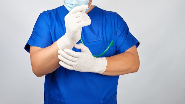 Male doctor in blue uniform puts on his hands white sterile latex gloves