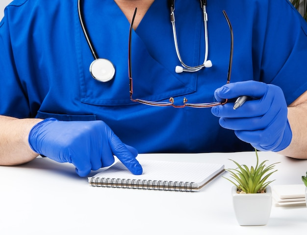 Male doctor in a blue uniform sits at a white table and writes in a paper notebook, wearing sterile gloves on his hands, concept of receiving patients in the office