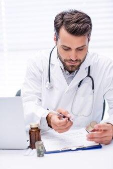 Male doctor checking medicine