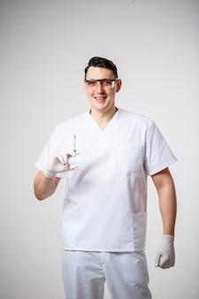 흰색 수술복을 입은 남성 의사 수석 의사. 클로즈업 초상화입니다. 주사가 있는 주사기를 들고 있습니다. 흰색 배경에 고립.