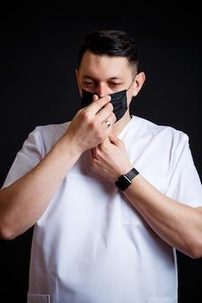 흰색 수술복을 입은 남성 의사 수석 의사. 클로즈업 초상화입니다. 바이러스에 대한 검은 의료 마스크를 착용
