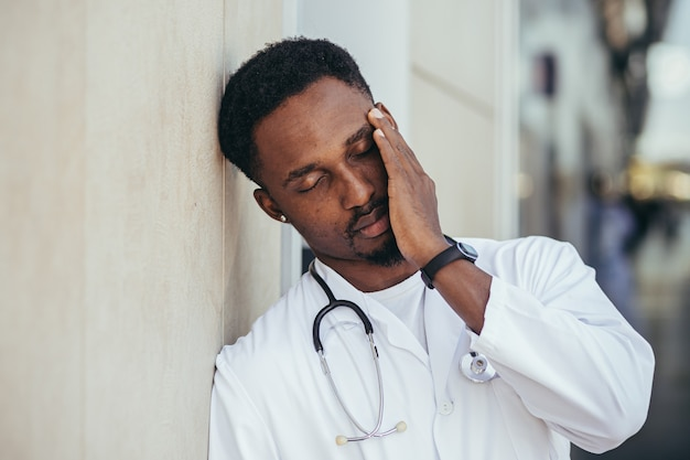 Male doctor at the clinic holding his head has health problems and tired after a hard day, depressed did not get the desired result, afro american doctor is sad