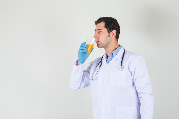Medico maschio che beve succo di frutta in camice bianco, guanti