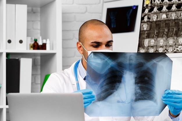 男性医師が病院のクローズアップで肺のレントゲン写真を調べる