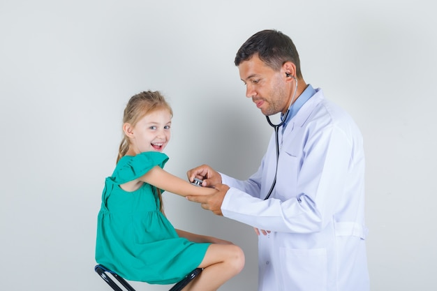 Male doctor examining little girl's arm with stethoscope in white uniform front view.