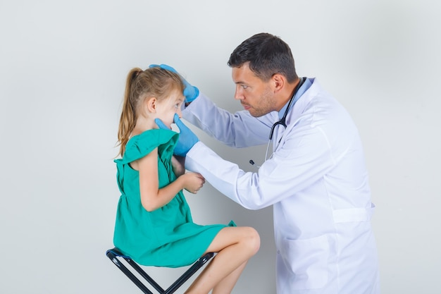 Врач-мужчина осматривает глаза маленькой девочки в белой униформе, перчатках и внимательно смотрит